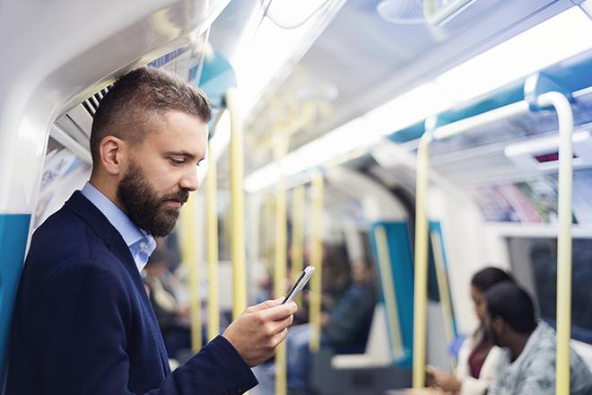 電車で携帯を触る男性