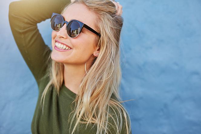 髪をかきあげて笑う女性