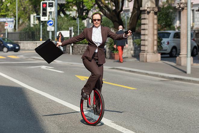 一輪車に乗って出勤する女性