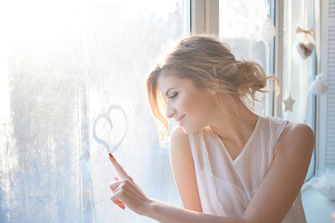 窓にハートを書く女性