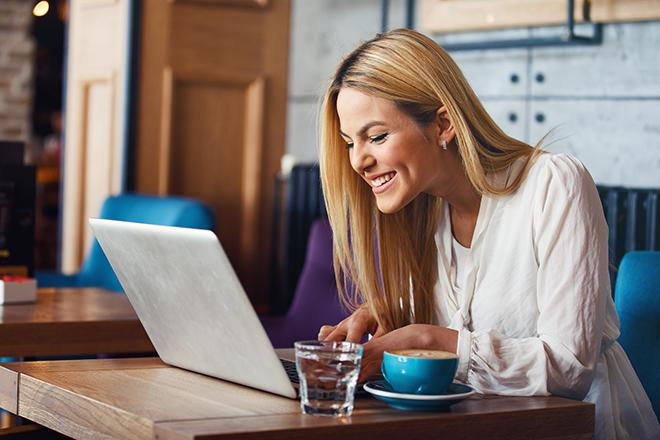 笑顔でパソコンに打ち込む女性