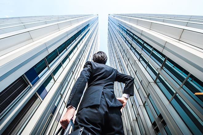 高層ビルを見上げるサラリーマン
