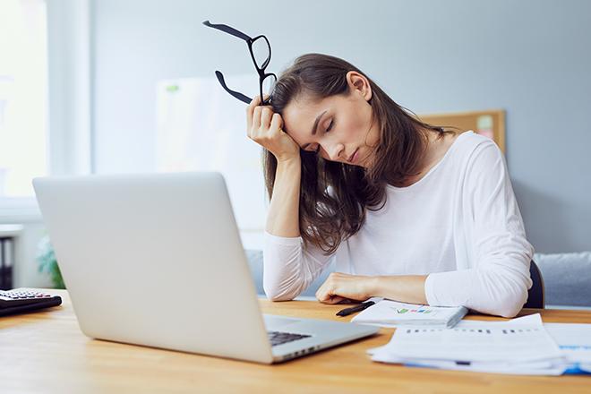 眠気で頭を抱える女性