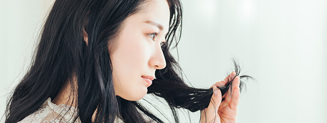 髪の先をいじる女性